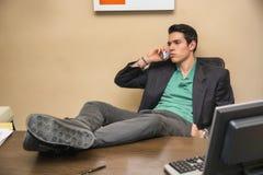 Pomyślny przystojny młody biznesmen przy biurkiem Zdjęcia Stock