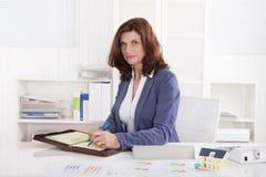 Pomyślny stary biznesowej kobiety obsiadanie przy biurem. Zdjęcia Stock