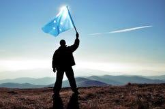 Pomyślny sylwetka mężczyzny zwycięzca macha Micronesia flagę na górze góry zdjęcia royalty free