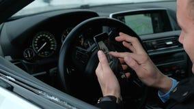 Pomyślny szanowany biznesmen przy kołem drogi samochód używa telefon zdjęcie wideo