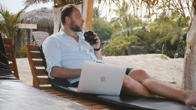 Pomyślny szczęśliwy zrelaksowany biznesmen z smartphone, laptopu i owocowego napoju obsiadaniem w plażowym holu krześle na wakacj zdjęcie wideo