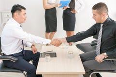 Pomyślny uścisk dłoni dwa biznesmena przy biurem obrazy royalty free