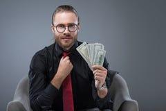 Pomyślny uśmiechnięty mężczyzna z pieniądze w ręki obsiadaniu w karle podczas gdy prostujący krawat, fotografia royalty free