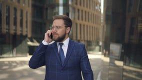 Pomyślny właściciel biznesu opowiada telefon, chodzi wzdłuż ulicy w stolicie zbiory