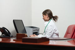 Pomyślna kobiety lekarka Pracuje Przy komputerem Obrazy Stock