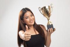 Pomy?lna m?oda azjatykcia kobieta trzyma trofeum przedstawienia kciuk w g?r? zdjęcie stock
