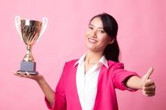 Pomy?lna m?oda azjatykcia kobieta trzyma trofeum przedstawienia kciuk w g?r? obrazy royalty free