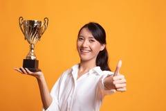 Pomy?lna m?oda azjatykcia kobieta trzyma trofeum przedstawienia kciuk w g?r? obraz stock