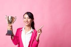 Pomy?lna m?oda azjatykcia kobieta trzyma trofeum punkt pusta przestrze? zdjęcie stock