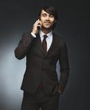 Pomyślny biznesmen opowiada na telefonie komórkowym Fotografia Stock