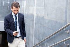 Pomyślny biznesmen patrzeje na jego smartphone w miasta str Obrazy Stock