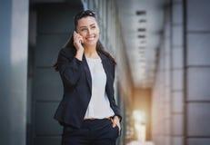 Pomyślny bizneswoman opowiada na telefonie komórkowym Zdjęcia Royalty Free