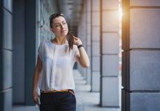 Pomyślny bizneswoman opowiada na telefonie komórkowym Zdjęcia Stock