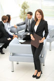 Pomyślna biznesowej kobiety pozycja z jej personelem w tle Obrazy Stock