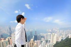 Pomyślny biznesowy mężczyzna patrzeje daleko od z miastem Zdjęcie Stock