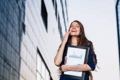 Pomyślny uśmiechnięty biznesmen, stoi przeciw tłu budynki trzyma skoroszytowy z sprzedażami sporządza mapę Miasto biznesowa kobie Obrazy Stock