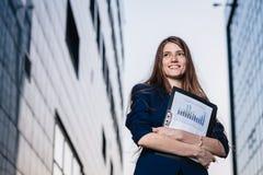 Pomyślny uśmiechnięty biznesmen, stoi przeciw tłu budynki trzyma skoroszytowy z sprzedażami sporządza mapę Miasto biznesowa kobie Fotografia Royalty Free
