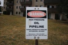 Ponaftowy rurociąg znak ostrzegawczy w zielonej trawiastej łące zdjęcia stock