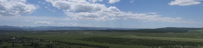 Ponarama of rural areas. With the settlement, mountains, the sky with clouds stock photography