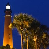 The Ponce Inlet Lighthouse glows on Florida Atlantic Coast. Palm trees stand in front of the Ponce Inlet Lighthouse giving a tropical feel to the scene Stock Photo