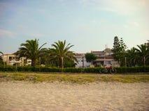 Poncez la plage, les palmiers, les villas et la bicyclette rouge dans Halkidiki, Grèce Photos stock