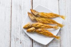 Poncez les poissons de merlans cuits à la friteuse avec le safran des indes et l'ail sur p blanc Image stock