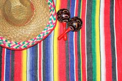 Mexico traditional cinco de mayo rug poncho fiesta with stripes. Poncho background sombrero Mexican traditional cinco de mayo rug fiesta with stripes maracas royalty free stock photo
