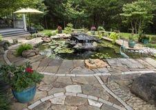 Pond с малыми водопадом, лилиями воды, цветочными горшками, и скульптурами птицы Стоковое Фото