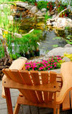 Pond. Natural stone pond and wooden patio chair as landscaping design element Stock Photos