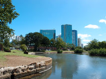 Pond in Ala Moana Beach Park with Condominiums towers across the. Waterway opens into pond in Ala Moana Beach Park surrounded by trees with Condominiums towers Royalty Free Stock Image