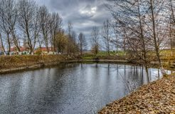 Pond in Autumn. Image of a fishing lake in autumn during a cloudy day Royalty Free Stock Image