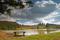 Pond and bench. Bench overlooking a pond, with dramatic clouds stock photography