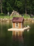 Pond with bird house on the backdrop of an alphine slide. Gorky park,Melitopol stock images