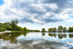 A pond with a cloudy sky. And trees Royalty Free Stock Photos