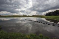 Pond com um passadiço e as nuvens antes da tempestade fotos de stock royalty free