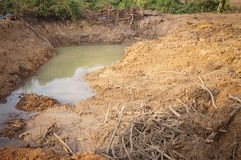 Pond Digging. Digging soil horizon area with reflection of tree and hill in or royalty free stock images