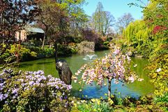 Pond in The Dingle, Shrewsbury. Bird statue on the edge of the pond in the Dingle formal gardens in Quarry Park during the Springtime, Shrewsbury, Shropshire Stock Images