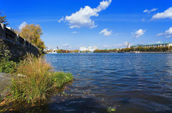 Pond, embankment and buildings Stock Image