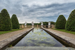 Pond with on the end the back of a four Roman statutes. Royalty Free Stock Photos