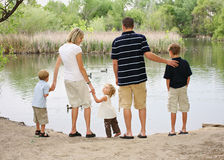 Pond Family. Young family of five standing together looking at duck pond in Spring Royalty Free Stock Photography