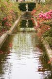 Pond in formal garden. Pond with blooming azalea and statue in formal garden Stock Image