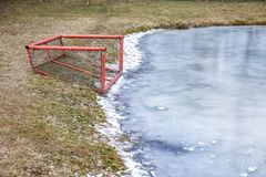 Self-made, red hockey gateway with the net. A pond with ice, a hockey gate on the shore; self-made, red hockey gateway with the net Royalty Free Stock Photo