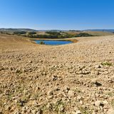 Pond for irrigation in Italy. Pond for irrigation between stubble fields in Italy. Plowed hills of Tuscany in the autumn. Plowed agricultural land in Italy Royalty Free Stock Images