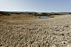 Pond for irrigation in Italy. Pond for irrigation between stubble fields in Italy. Plowed hills of Tuscany in the autumn. Plowed agricultural land in Italy Royalty Free Stock Photography