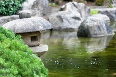 Pond in a Japanese garden with a traditional stone lantern in the foreground stock photography
