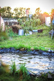 Pond in landscape design with swing and grass Royalty Free Stock Photos