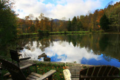 Pond in the mountains. A mountain scene with a pond and chairs Royalty Free Stock Images