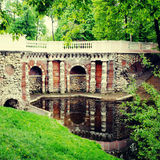 Pond with old beautiful stone grotto in summer park Stock Images