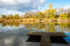 Pond with pier in autumn royalty free stock photography