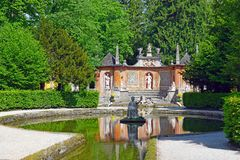 Pond in Public Gardens of Hellbrunn Palace in Salzburg. Salzburg, Austria - May 25, 2019 : sculptures at the pond in Public Gardens of Hellbrunn Palace Schloss royalty free stock image